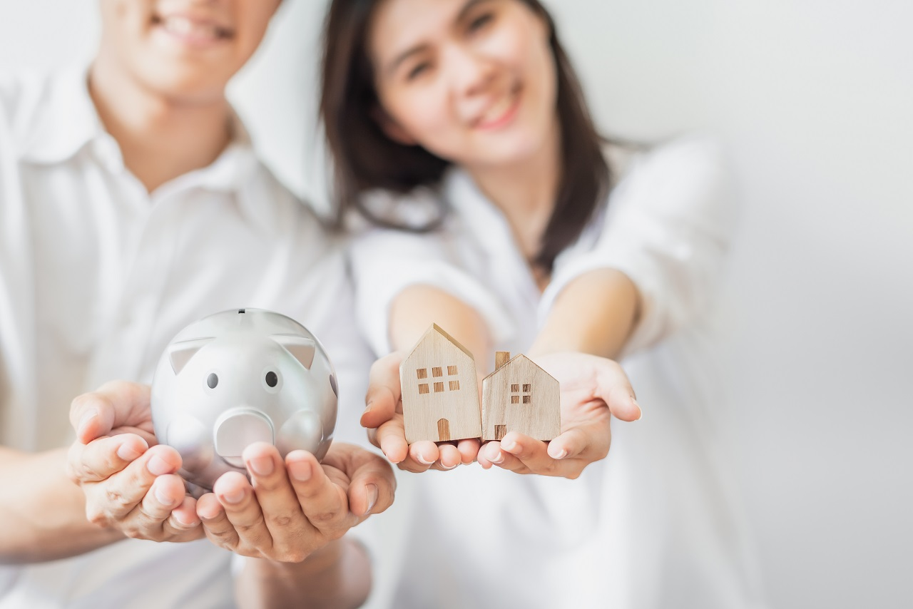 A couple dressed in white holding a piggy bank and a cardboard house