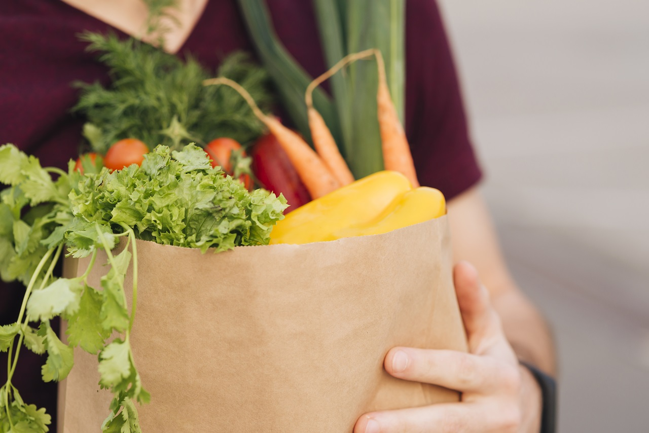 Close up of a person carrying a paper bag full of groceries