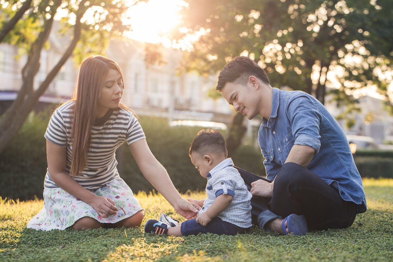 A young asian family sitting on the grass playing with their young son