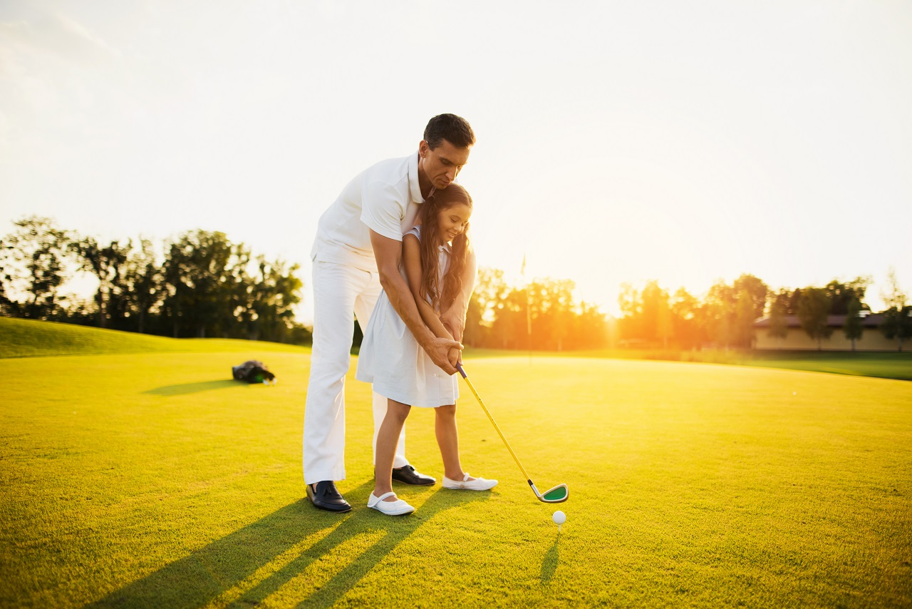 A dad teaching his daughter how to golf