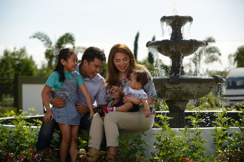 Family sitting on a fountain made by the best housing developer in the philippines